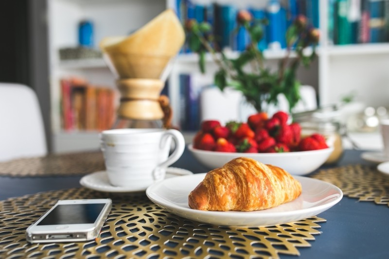 croissant-on-table-with-mobile-phone-and-strawberries